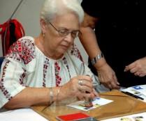 """Mirta Rodríguez (sentada), madre de Antonio Guerrero (Tony), uno de Los Cinco Antiterroristas cubanos presos en cárceles de los EE.UU, cancela un sello postal, durante el acto de inauguración de la exposición """"Cubanía en Mariposas"""", de su hijo Tony, el 19 de septiembre de 2011, en el museo Nacional de Historia Natural de Cuba, en La Habana AIN FOTO/Oriol de la Cruz ATENCIO"""